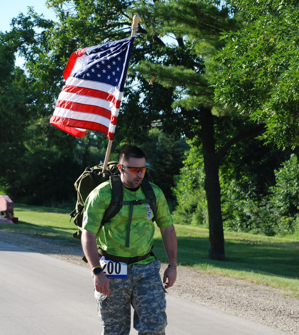 Runner carries the American Flag during the Run 4 Troops marathon